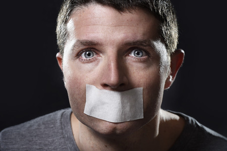 oppress: attractive young man with mouth sealed on duct tape to prevent him from speaking keeping him mute and censored in freedom of speech and expression concept