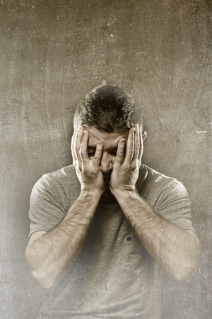 male headache: young man in stress suffering depression, headache , migraine , mental  breakdown and pain on grunge studio background covering face with hands in crisis