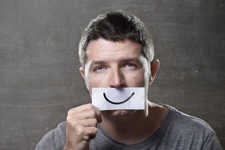 forcing: young depressed man lost in sadness and sorrow holding paper with smiley on his mouth as society forcing him to hide his pain in depression and lost of hope concept Stock Photo