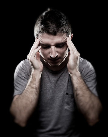 male headache: young man suffering migraine and headache in intense pain feeling desperate and sick with hands on tempo in stress isolated on black studio background