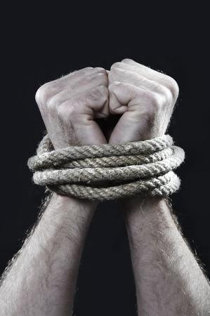 diritti umani: bianco mani uomo avvolto con corda attorno ai polsi di prigionia, vittima di abusi, schiavo del lavoro, il rispetto dei diritti umani e il concetto di sfruttamento isolato su sfondo nero Archivio Fotografico