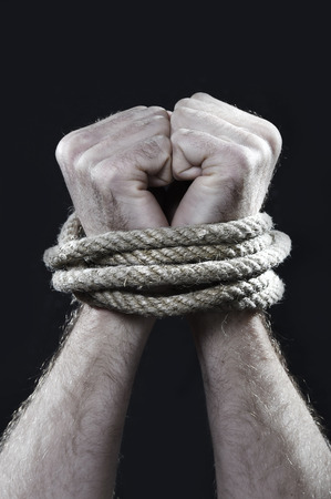 derechos humanos: blancas manos del hombre envuelto con una cuerda alrededor de las muñecas en cautiverio, víctima abusados, esclavo del trabajo, el respeto a los derechos humanos y el concepto de explotación aislado en fondo negro