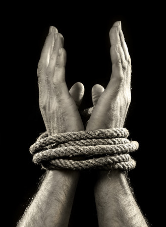 slave labor: white man hands wrapped with rope around wrists in captivity , victim abused , slave of work , respect for human rights and exploitation concept isolated on black background Stock Photo