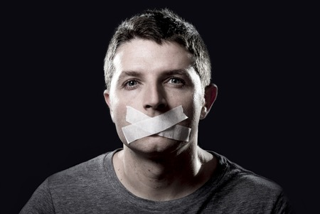 opposition: attractive young man with mouth and lips sealed on tape to prevent from speaking free keeping him mute and censored in freedom of speech and expression concept