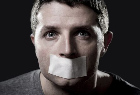 mouth closed: attractive young man with mouth and lips sealed on tape to prevent from speaking free keeping him mute and censored in freedom of speech and expression concept