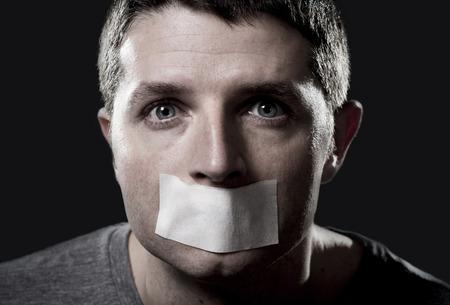 attraktive junge Mann mit Mund und Lippen auf Band versiegelt, um zu sprechen frei halten ihn stumm zu verhindern und die Freiheit der Rede und des Ausdrucks Konzept zensiert