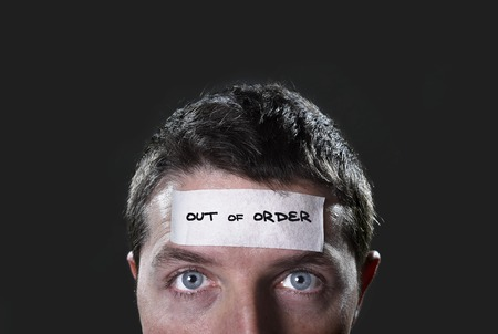 mental illness: young man with blue eyes and tape text out of order on forehead in empty mind and blank brain concept,  lack of ideas, creativity and mentally tired, overwhelmed and stressed Stock Photo