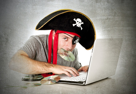 piracy: man dressed as pirate with CD in his mouth at computer laptop downloading music files and movies in copyright violation and illegal internet piracy concept