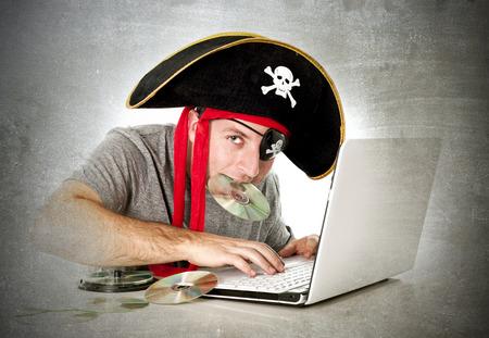 Man verkleed als piraat met CD in zijn mond op de computer laptop downloaden van muziekbestanden en films in schending van het auteursrecht en illegale internet piraterij-concept Stockfoto - 35024180
