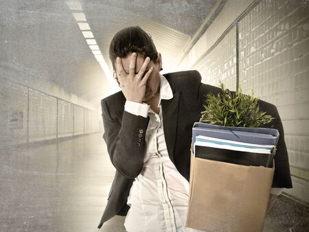 desperate depressed businesswoman fired from job carrying office belongings in cardboard box crying sad in grunge tunnel background in financial crisis and work loss concept photo