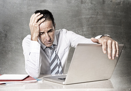 angry: desperate tired senior businessman in crisis working on computer laptop at office desk in stress under pressure facing work problems on grunge studio edition