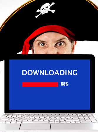 scammer: Young man in pirate costume and Computer laptop representing illegal downloads, movies and music downloading and copyright violation isolated on white background