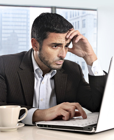 exhausted worker: attractive Hispanic businessman working with computer looking stressed and worried facing work issue sitting at business district office desk with cup of coffee