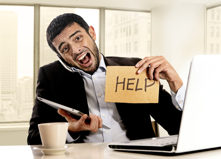 desperate businessman in stress holding help sign multitasking overwhelmed in business district office sitting at desk with computer laptop, digital pad and mobile phone Stock Photo
