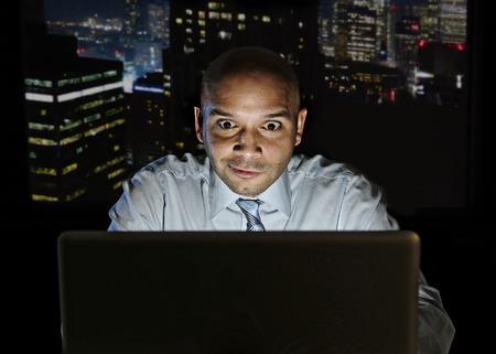 verslaafde zakenman alleen 's nachts zitten op kantoor computer laptop kijken naar porno, online gokken of laat aan het werk in de verslavingszorg begrip