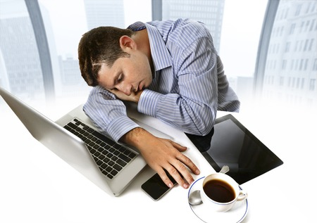 overworked businessman wearing blue shirt asleep at work tired and overloaded sitting with computer laptop, mobile phone and coffee cup in business district office photo