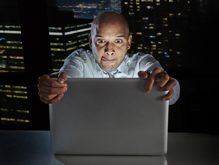internet porn: addict businessman alone at night sitting at office computer laptop watching porn or online gambling isolated on black background on internet chat addiction concept