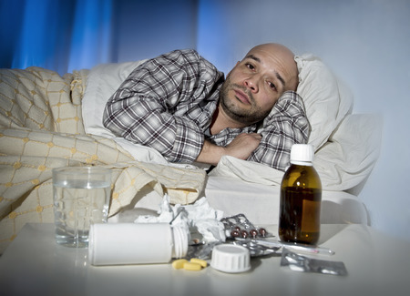 home health care: sick wasted man lying in bed at home wearing pajama suffering cold and winter flu virus having medicine and tablets in health care concept in tired face expression Stock Photo