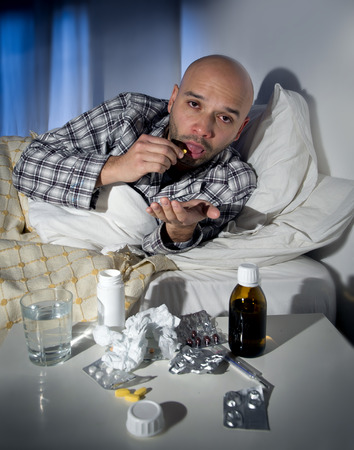 home health care: sick wasted man lying in bed at home wearing pajama suffering cold and winter flu virus taking medicine tablets in health care concept in tired face expression Stock Photo