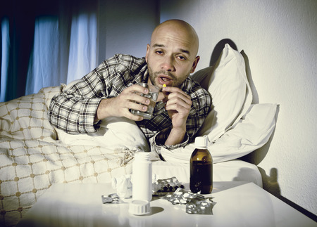wasted: sick wasted man lying in bed at home wearing pajama suffering cold and winter flu virus taking medicine tablets in health care concept in tired face expression Stock Photo