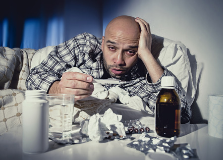 flu: sick wasted man lying in bed wearing pajama suffering cold and winter flu virus having medicine tablets in health care concept looking temperature on thermometer Stock Photo