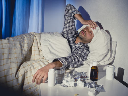 wasted: sick wasted man lying in bed suffering cold , headache and winter flu virus having lots of medicine , pills and tablets in health care concept