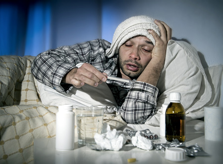 wasted: sick wasted man lying in bed wearing pajama suffering cold and winter flu virus having medicine tablets in health care concept looking temperature on thermometer Stock Photo