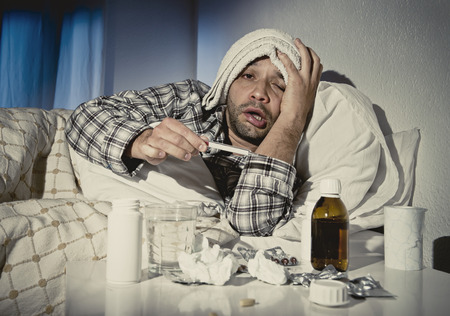 fever: sick wasted man lying in bed wearing pajama suffering cold and winter flu virus having medicine tablets in health care concept looking temperature on thermometer Stock Photo