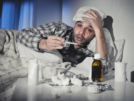 personas enfermas: hombre perdido enfermo acostado en la cama vistiendo pijama sufriendo virus de la gripe fr�o y el invierno con tabletas de medicina en concepto de atenci�n de salud en busca de temperatura en el term�metro Foto de archivo