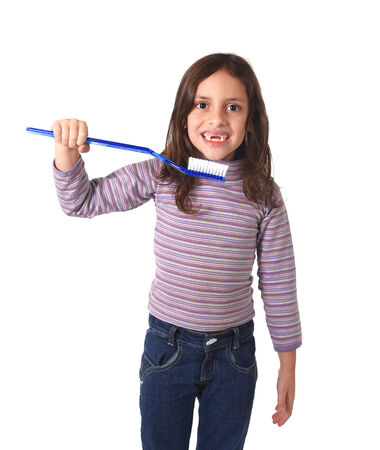 toothed: sweet cute 7 years old girl smiling gap toothed with huge toothbrush in her hand playing cleaning her mouth in dental care concept isolated on white background Stock Photo