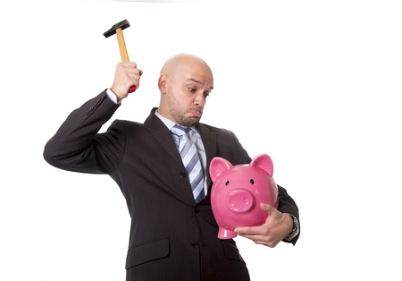 bald Hispanic businessman with hammer in his hand holding pink piggybank ready to break the piggy bank and take money and savings out isolated on white background photo