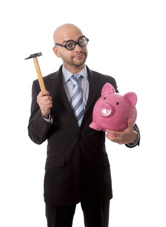 bald nerdy businessman with geek glasses holding pink piggybank on his hand ready to break piggy bank with hammer and take money out isolated on white background photo