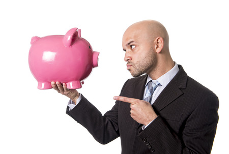 businessman holding piggybank face to face pointing the piggy bank with his finger as a you better be full of money warning isolated on white background photo