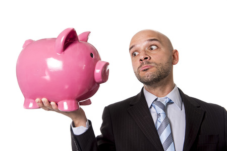 businessman holding piggybank face to face looking the piggy bank in the eye as a you better be full of money warning isolated on white background photo
