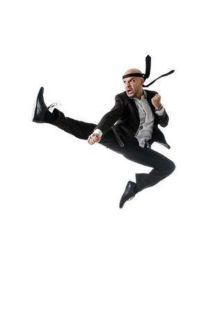 karate fighter: funny aggressive businessman wearing suit jumping on the air in kung fu kick or karate flying attack isolated on white background in business strength and competition concept