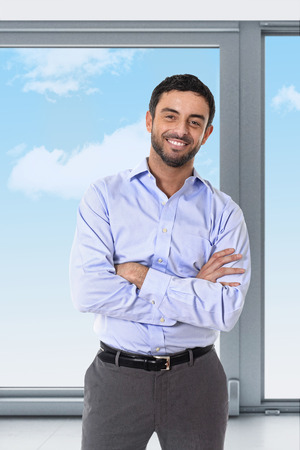 office window view: young attractive business man standing in corporate portrait smiling with folded arms in smart casual shirt and suit trousers in front of blue sky office window view