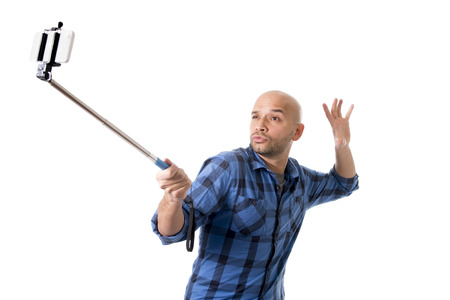 young Hispanic man in casual shirt having fun shooting mobile phone selfie picture or recording video holding stick playing with face expression isolated on white background Stock Photo