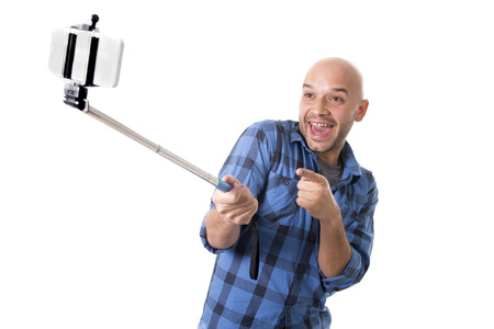 to stick: young Hispanic man in casual shirt having fun shooting mobile phone selfie picture or recording video holding stick playing with face expression isolated on white background Stock Photo