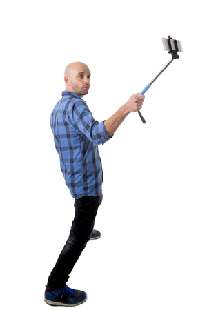 are taking: young Hispanic man in casual shirt having fun shooting mobile phone selfie picture or recording video holding stick playing with face expression isolated on white background Stock Photo