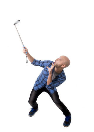 subjective: young Hispanic man in casual shirt having fun shooting mobile phone selfie picture or recording video holding stick playing with face expression isolated on white background Stock Photo