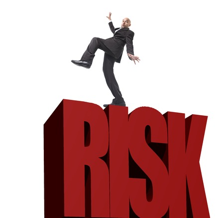 risk ahead: businessman in stress walking on the edge taking big financial risk trying to keep balance and step ahead without falling down isolated on white background