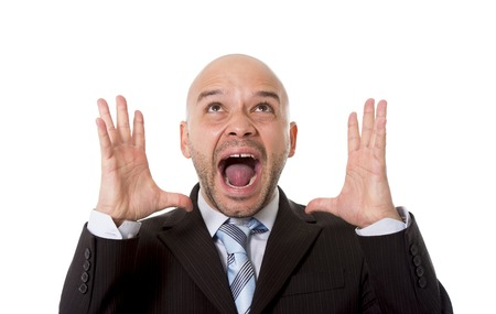 overwork: desperate Brazilian bald businessman screaming and shouting crazy stress with mouth open and mad face expression in overwork and business crisis concept