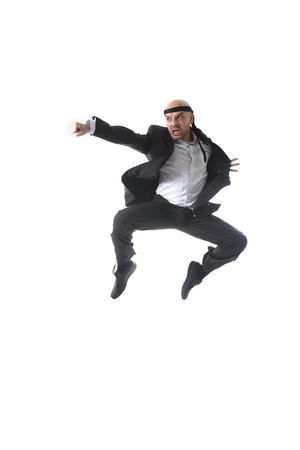 fu: spectacular aggressive businessman wearing suit jumping on the air in kung fu fist or karate flying punch attack isolated on white background in business competition concept