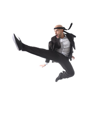 aggressive people: funny aggressive businessman wearing suit jumping on the air in kung fu kick or karate flying attack isolated on white background in business strength and competition concept