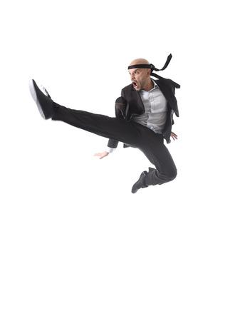 patada: negocios agresivo divertido el uso de traje de salto en el aire en el kung fu o karate patada ataque del vuelo aislado sobre fondo blanco en la fuerza empresarial y el concepto de competencia