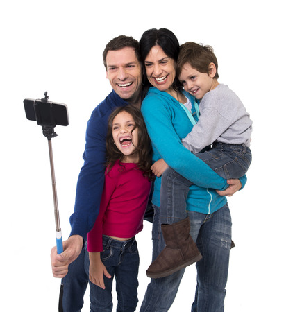 sticks: young happy Brazilian family mother and father taking selfie photo with mobile phone and stick playing with little son and daughter having fun all together Stock Photo