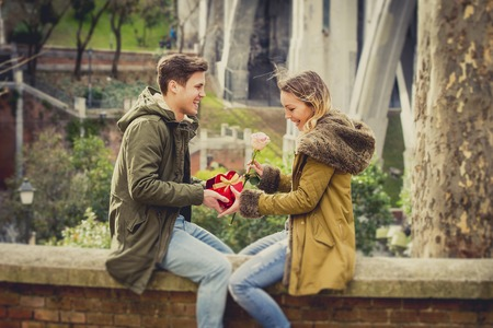 human relationship: couple in love kissing on street celebrating Valentines day with girl receiving heart shaped box present in city park urban background