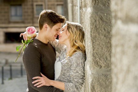 kissing couple: candid portrait of beautiful European couple with rose in love kissing on street alley celebrating Valentines day with passion against stone wall on urban background Stock Photo