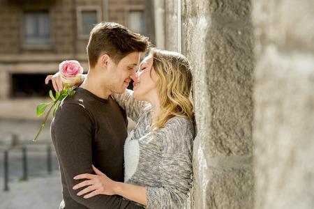novios besandose: sincero retrato de la bella pareja Europea con la rosa de enamorados bes�ndose en el callej�n de la calle celebrando el d�a de San Valent�n con pasi�n contra la pared de piedra en el fondo urbano