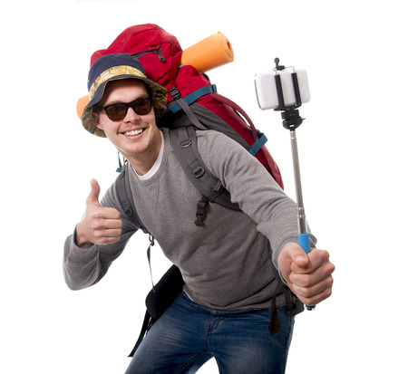 adventure: young attractive  backpacker tourist taking selfie photo with stick carrying backpack ready for travel and adventure on vacations route isolated on white background Stock Photo